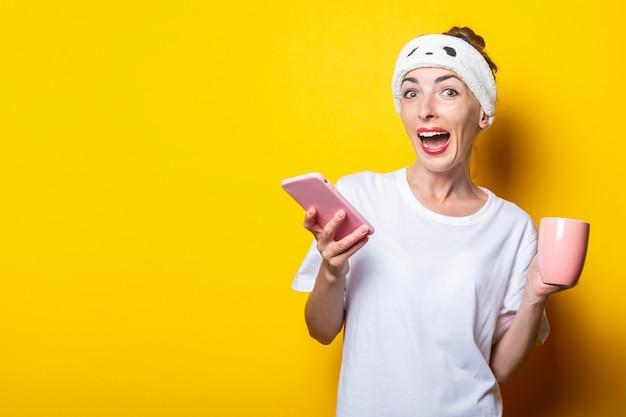 Радостная удивленная молодая девушка в повязке с телефоном и чашкой кофе на желтом фоне