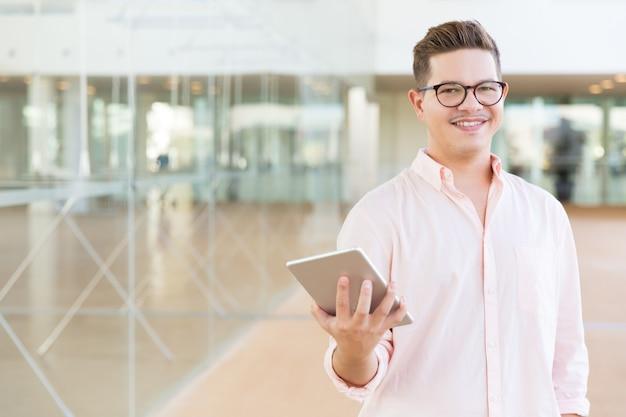 高速接続に満足しているメガネのうれしそうなタブレットユーザー