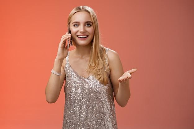 銀色のスタイリッシュなドレス、赤い背景を身に着けているパーティーの後に新鮮な噂を広く語って笑って面白がって笑っている友人のスマートフォンを身振りで示す楽しいおしゃべりな発信魅力的なブロンドの女性。
