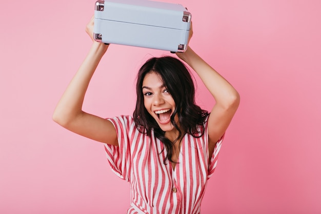 Joyful tanned girl with cheerful mood is dancing with briefcase. lady in striped top smiles broadly.