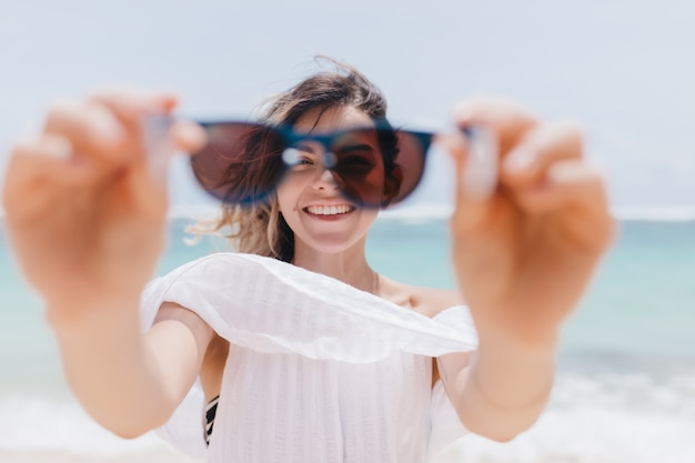 Joyful tanned woman playfully posing with sunglasses on sea. outdoor photo of pretty young woman fooling around at beach.