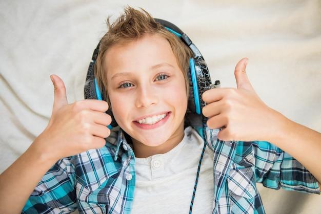 Радостный мальчик-подросток, слушающий музыку в синем наушнике