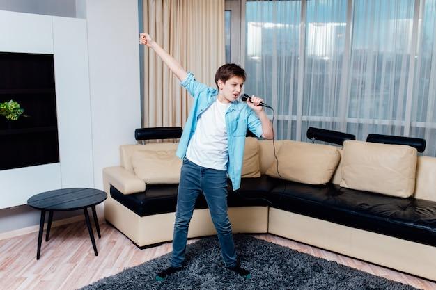 음악을 듣고 좋아하는 노래를 노래하는 즐거운 십 대 소년.