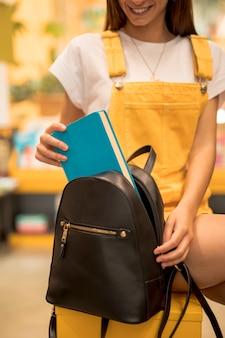 Joyful teen schoolgirl taking book from backpack
