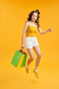 Радостная летняя девочка-подросток несет сумки и прыгает в воздухе на оранжевом фоне, снимок в полный рост с копией пространства