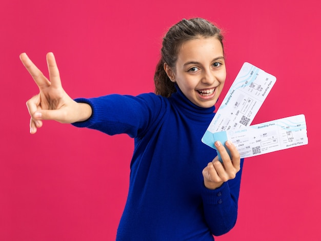 Joyful teenage girl holding airplane tickets looking at front doing peace sign isolated on pink wall