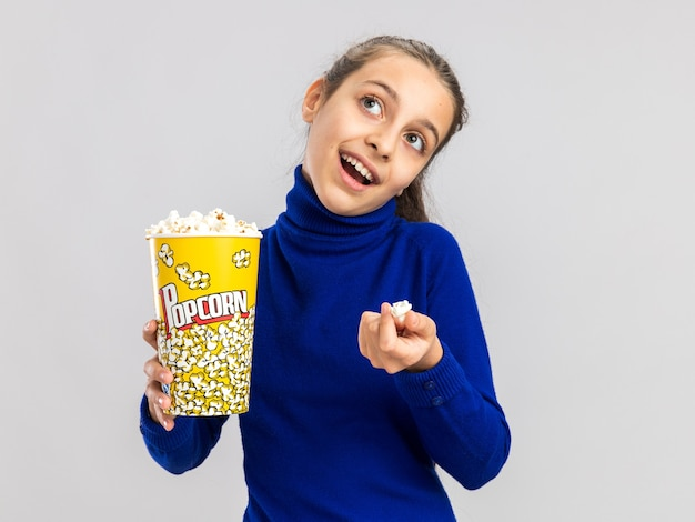 Joyful teenage girl holding bucket of popcorn and popcorn piece looking up isolated on white wall with copy space