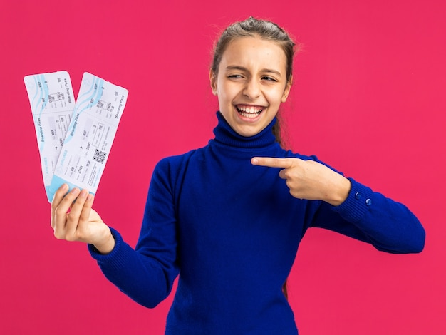 ピンクの壁に分離された飛行機のチケットを指差して見ているうれしそうな10代の少女