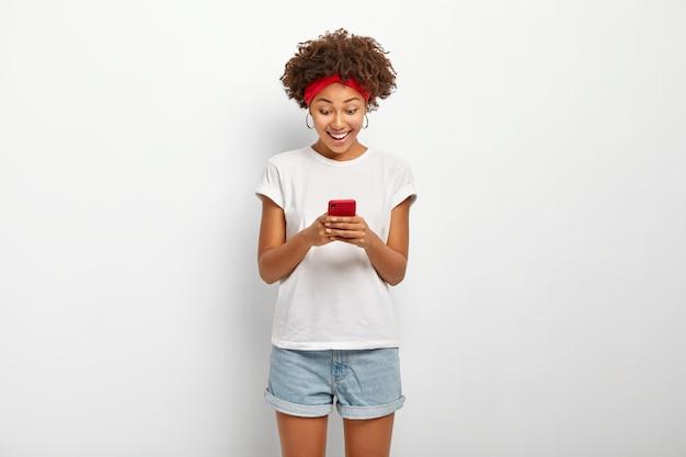 즐거운 십대 소녀는 휴대 전화를 보유하고 귀걸이, 캐주얼 복장을 착용합니다.