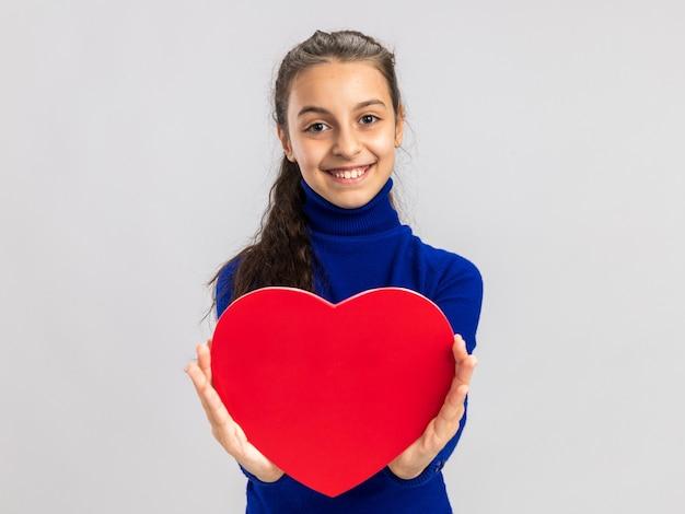 복사 공간이 있는 흰색 벽에 격리된 전면을 바라보는 카메라를 향해 심장 모양을 기지개하는 즐거운 10대 소녀
