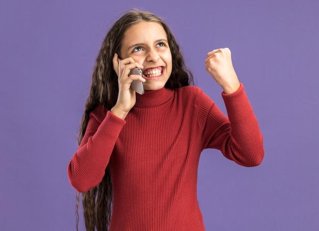 Радостная девочка-подросток разговаривает по телефону, глядя вверх, делая жест да, изолированные на фиолетовой стене