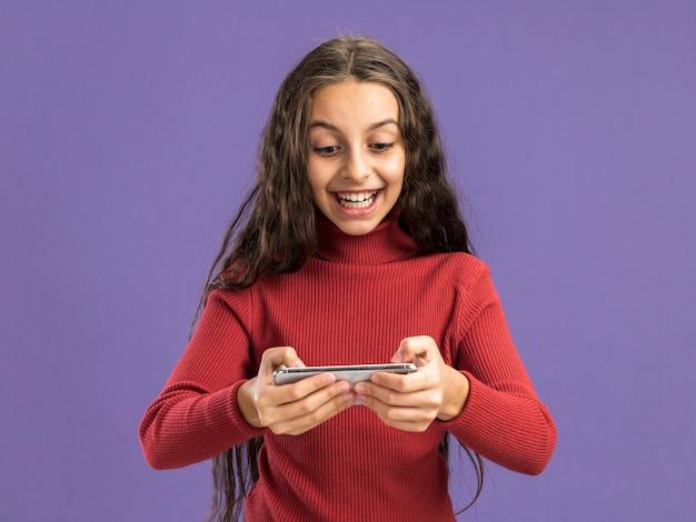 Радостная девочка-подросток с помощью своего телефона, изолированного на фиолетовой стене