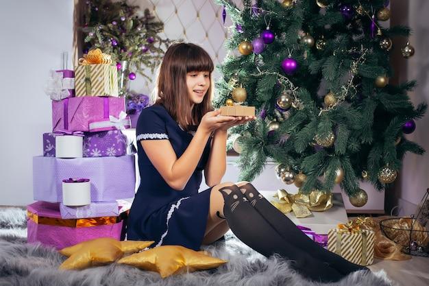 그의 손에 선물을 가진 즐거운 십 대 소녀는 크리스마스 트리 근처에 앉아있다.