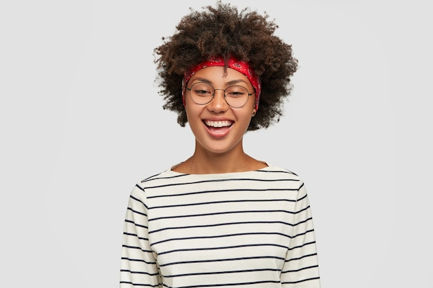 Joyful teenage girl with afro haircut rejoices discounts in shop, wants to buy new outfit, wears striped casual sweater, optical glasses