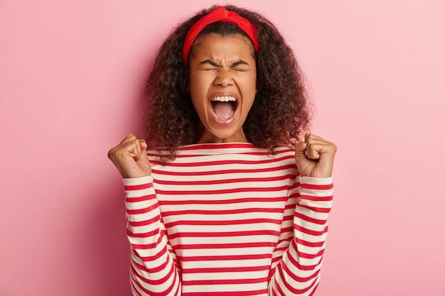 줄무늬 빨간 스웨터에 포즈 곱슬 머리를 가진 즐거운 십 대 소녀