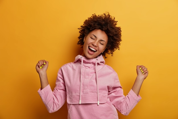 Joyful teenager dances carefree, feels upbeat, being champion, makes fists bump, closes eyes and smiles broadly, dressed in casual velvet hoodie, rejoices triumph, moves against yellow wall.