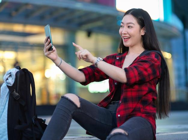 Радостный подросток видеозвонок со своими друзьями перед городским торговым центром молодой турист, делающий селфи