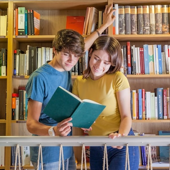 Joyful teenagers reading book in library