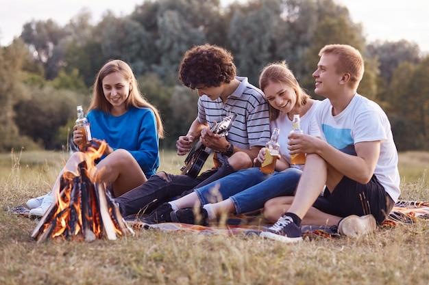 うれしそうな10代の若者が火の近くの地面に互いに近くに座って、一緒にピクニックをし、アコースティックギターを演奏し、何かを祝います
