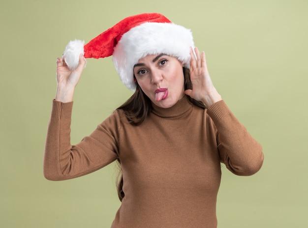 Радостная наклонная голова молодая красивая девушка в новогодней шапке показывает язык на оливково-зеленом фоне