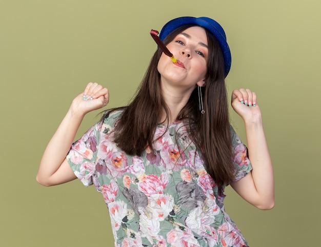 オリーブグリーンの壁に分離されたはいジェスチャーを示すパーティーハットを吹くパーティー笛を身に着けているうれしそうな傾いた頭の若い美しい少女