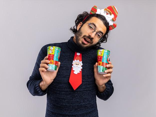 Радостный наклонив голову молодой красивый парень в рождественском галстуке с обручем для волос, держащий рождественские чашки, изолированные на белом фоне
