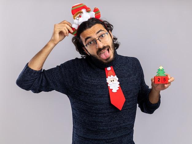 흰색 배경에 고립 된 혀를 보여주는 크리스마스 장난감을 들고 머리 후프와 크리스마스 넥타이를 착용하는 즐거운 틸팅 머리 젊은 잘 생긴 남자