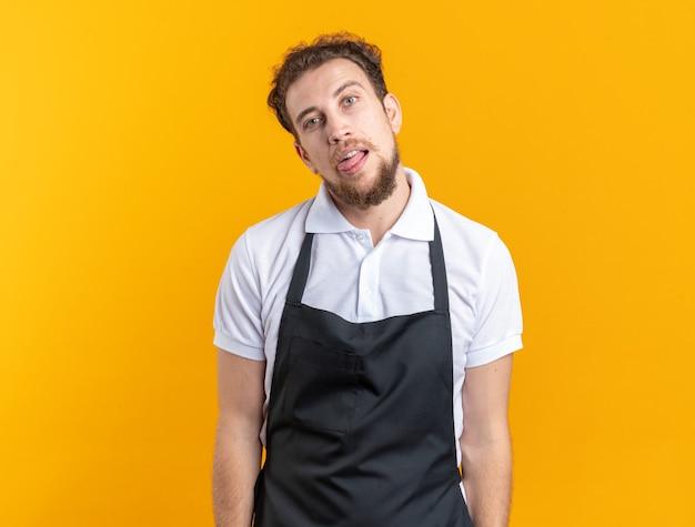 노란색 벽에 고립 된 혀를 보여주는 유니폼을 입고 즐거운 기울이기 머리 젊은 남성 이발사