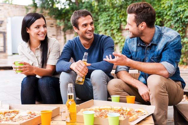 友達との楽しい時間。屋外に座ってビールを飲み、お互いに話している3人の幸せな若者