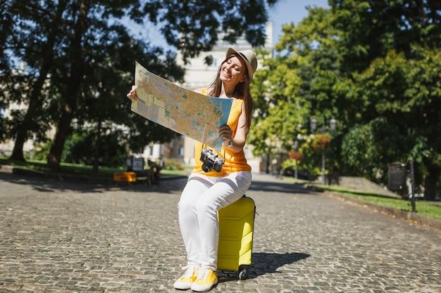 여행가방에 앉아 캐주얼한 옷을 입은 즐거운 여행자 관광 여성은 도시 야외에서 도시 지도 검색 경로를 찾고 있습니다. 주말 휴가를 여행하기 위해 해외로 여행하는 소녀. 관광 여행 라이프 스타일.