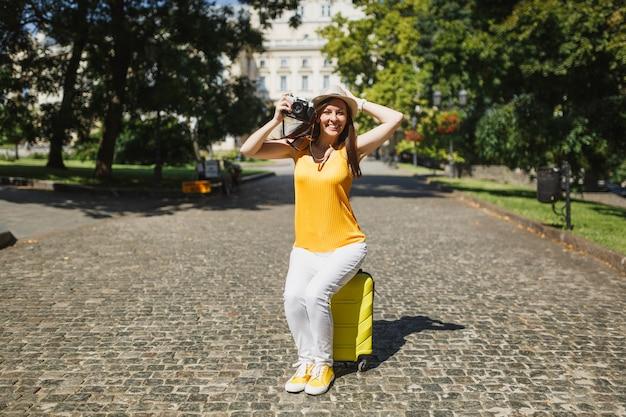 여행 가방에 앉아 모자를 쓴 즐거운 여행자 관광 여성은 도시 야외에서 복고풍 빈티지 사진 카메라로 사진을 찍습니다. 주말 휴가를 여행하기 위해 해외로 여행하는 소녀. 관광 여행 라이프 스타일.
