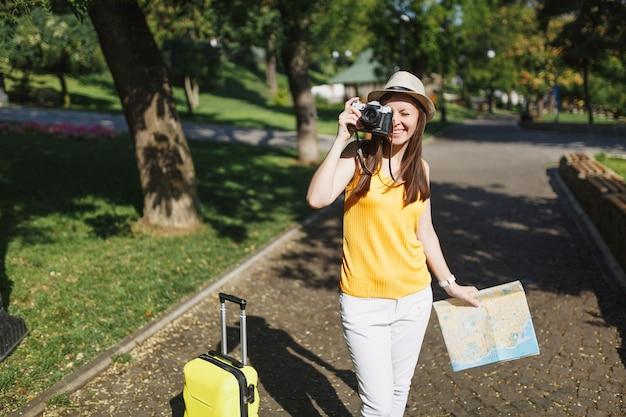 여행 가방 도시 지도가 있는 모자를 쓴 즐거운 여행자 관광 여성은 도시 야외에서 복고풍 빈티지 사진 카메라로 사진을 찍습니다. 주말 휴가를 여행하기 위해 해외로 여행하는 소녀. 관광 여행 라이프 스타일.