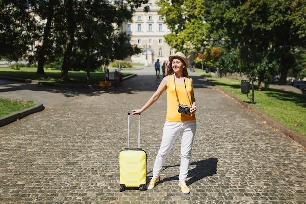 노란색 캐주얼 옷 모자를 쓴 즐거운 여행자 관광 여성, 여행가방 복고풍 빈티지 사진 카메라가 도시 야외에서 걸어갑니다. 주말 휴가를 여행하기 위해 해외로 여행하는 소녀. 관광 여행 라이프 스타일.