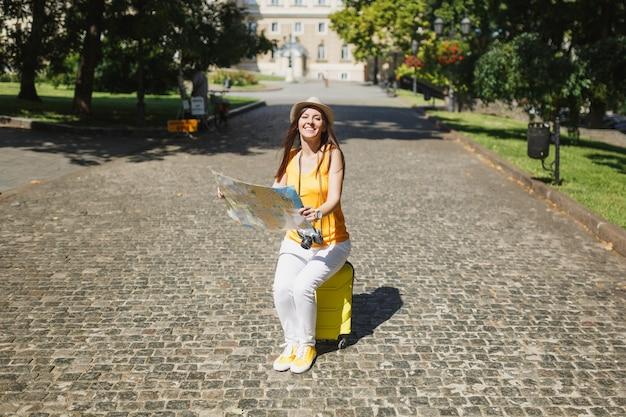 노란색 옷을 입은 즐거운 여행자 관광 여성, 모자는 도시 야외에서 도시 지도 검색 경로를 들고 여행 가방에 앉아 있습니다. 주말 휴가를 여행하기 위해 해외로 여행하는 소녀. 관광 여행 라이프 스타일.