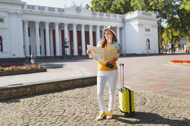 黄色い夏のカジュアルな服を着た楽しい旅行者の観光客の女性、屋外の街の都市地図検索ルートを探しているスーツケース付きの帽子。週末の休暇で海外旅行する女の子。観光の旅のライフスタイル。