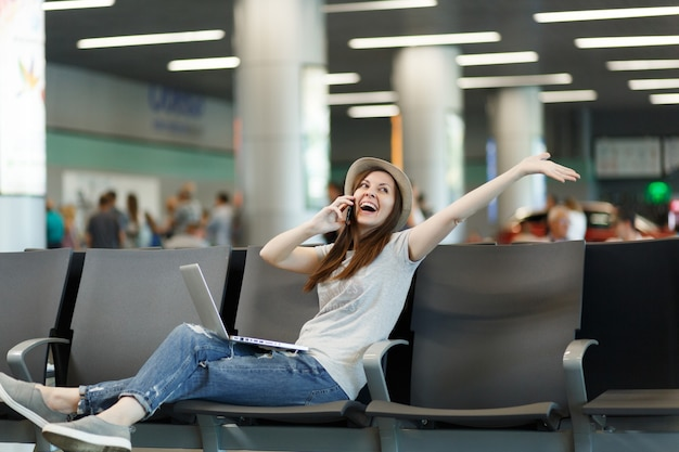 Joyful traveler tourist woman work on laptop talk on mobile phone call friend booking taxi hotel spread hands wait in lobby hall at airport