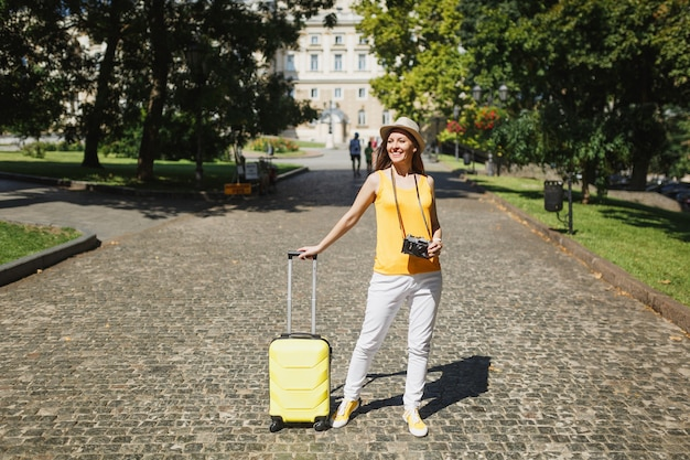 Joyful traveler tourist woman in yellow casual clothes hat with suitcase retro vintage photo camera walk in city outdoor. girl traveling abroad to travel on weekend getaway. tourism journey lifestyle.