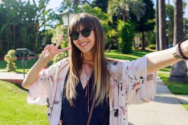 Радостная путешествующая улыбающаяся длинноволосая девушка делает автопортрет на улице лос-анджелеса.