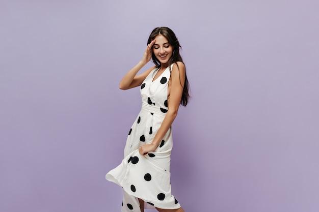 Gioiosa ragazza alla moda con una lunga acconciatura scura in abito bianco alla moda che sorride e guarda in basso sul muro lilla isolato