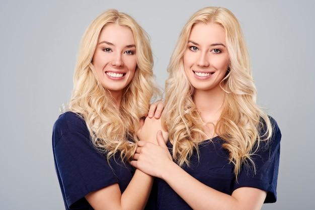 青いネイビーシャツのうれしそうな双子