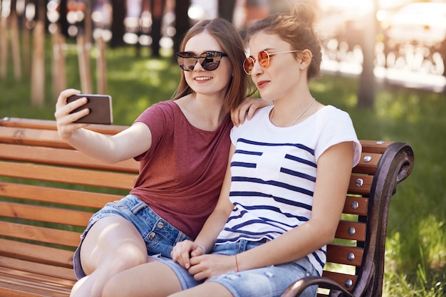 Joyful two girls make selfie portrait with modern cell phone, sit closely to each other on bench in park, dressed in casual summer clothes, have fun together. people, youth and technology concept