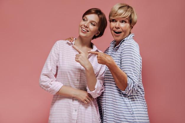 Радостные две дамы с короткими волосами в полосатой розовой и синей летней одежде улыбаются и показывают место для текста на изолированном фоне.