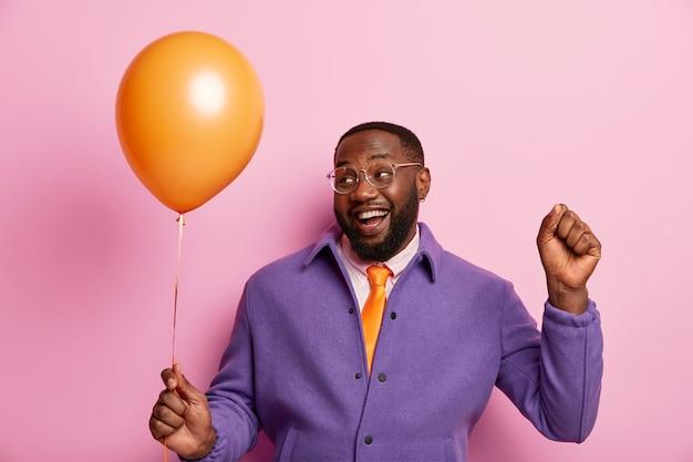 うれしそうな無精ひげを生やしたふっくらとした男は何かを祝い、遊び心のある気分を持ち、拳を上げ、膨らんだ風船を持っています