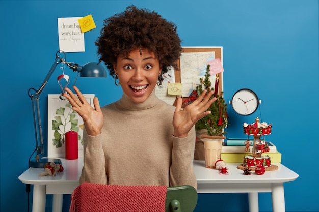 Joyful upbeat dark skinned woman has both palms raised, sits at desktop with christmas tree and other holiday attributes
