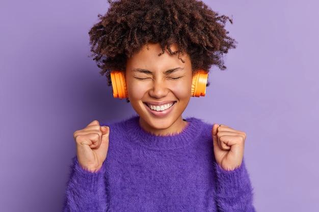アフロの髪を持つうれしそうな明るい10代の少女は、くいしばられた握りこぶしを上げますカジュアルなジャンパーを着用しますヘッドフォンでお気に入りの音楽を聴きます幸運な日を祝います