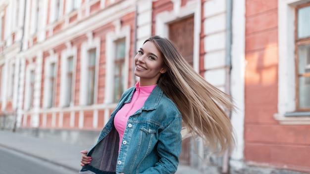 트렌디 한 핑크 탑의 빈티지 청바지 재킷에 금발 긴 머리를 가진 귀여운 미소로 즐거운 도시 젊은 여성이 거리에있는 건물 근처 포즈. 꽤 행복 한 소녀는 여름 날에 도시에서 산책.