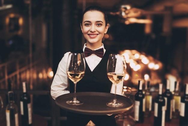 Joyful waitress holding tray with glasses of white wine.