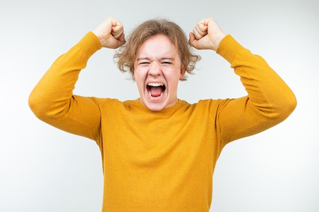 Joyful wavy blond guy in a yellow sweater on a white background
