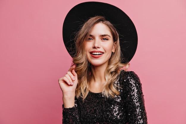 Радостная хорошо одетая девушка позирует в черной шляпе. утонченная европейская дама, стоящая на пастельной стене.