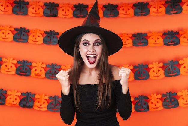 주황색 호박 벽 위에 고립된 승자로 비명을 지르는 검은 할로윈 의상을 입은 즐거운 마녀 소녀